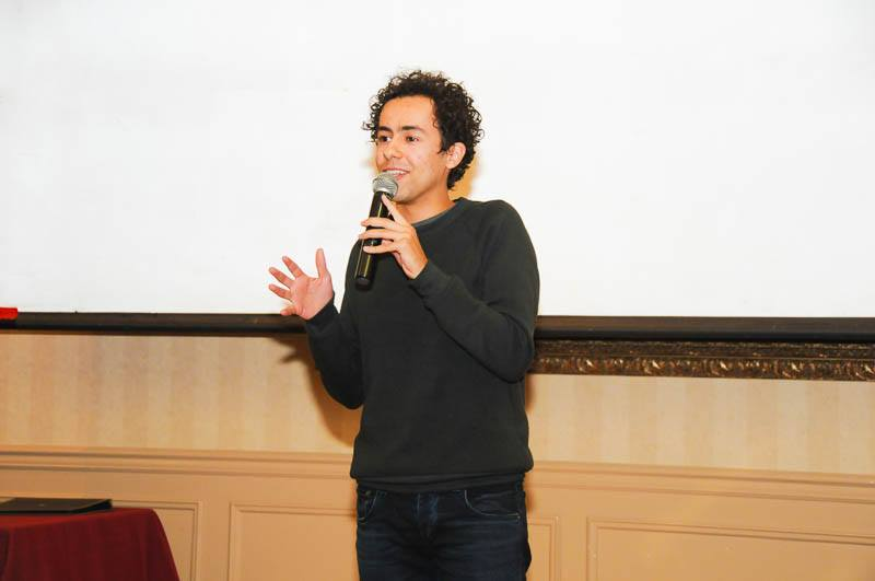 young man speaking at semi annual networking dinner
